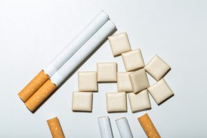 A close up of some cigarettes and nicotine chewing gum on a white background